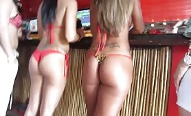 Round asses in string bikini at the-beach bar